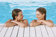 Two young women in pool at poolside talking, front view