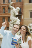 Young couple with guidebook looking at monuments on street in Rome, Italy, head and shoulders