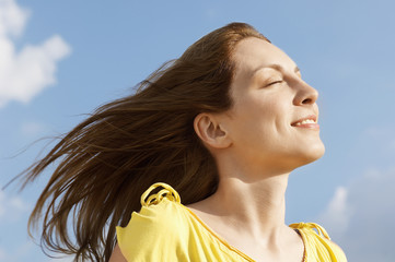 Young woman outdoors enjoying wind on face, close up