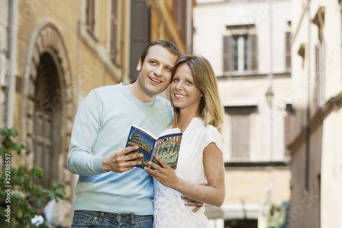 Couple on street in Rome, Italy, holding guidebook, front view