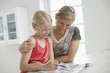 Mother and Daughter Colouring in book at kitchen table