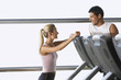 Man and Woman Talking by treadmill in Health Club