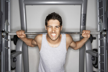 Man Grimacing while Lifting Weights on weight machine, portrait