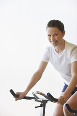 Young Woman Using Exercise Bike, portrait