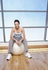 Woman sitting on Exercise Ball in gym, portrait