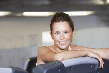 Young Woman resting on treadmill at Health Club, portrait
