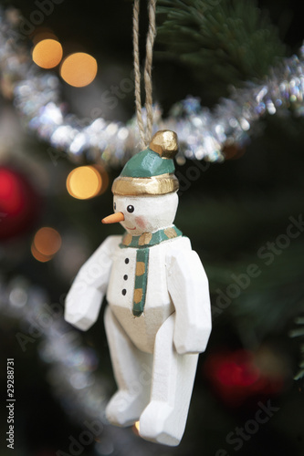 Snowman christmas decoration hanging from christmas tree, close up