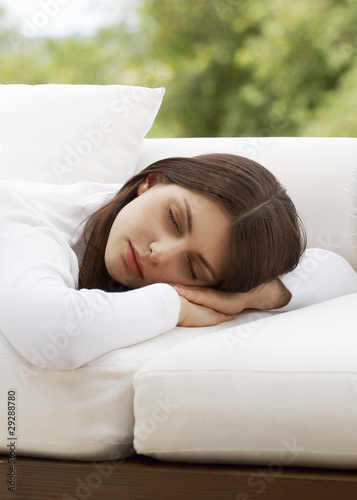 Young woman sleeping on sofa, portrait