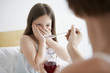 Mother giving cough syrup to reluctant daughter in bedroom