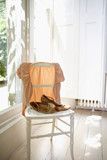 Female jacket and shoes on chair indoors by window