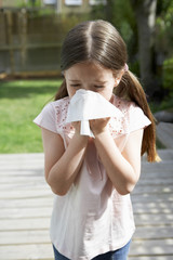 Little girl in backyard blowing nose