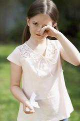 Little girl with cold rubbing eyes in backyard, portrait