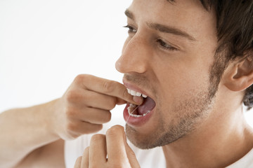 Mid-adult man flossing teeth in bathroom, close up