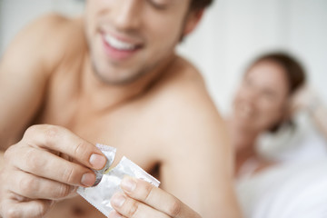 Couple in bed, man opening condom, close up of condom