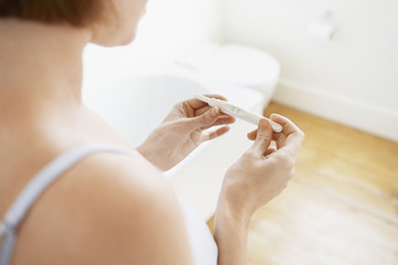 Woman Checking Pregnancy Test Kit, mid-section, focus on hands