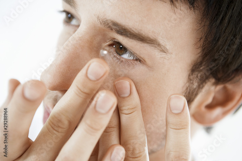 Man inserting contact lens, close up