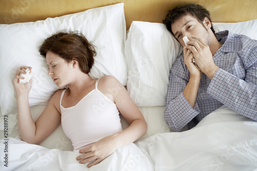 Couple with Colds Lying in Bed, high angle view