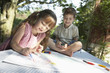 Young boy and girl drawing on table in back garden