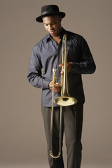 Trombonist standing wearing hat, looking at trombone