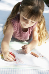 Young girl lying on table in back yard drawing