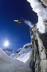 Skier jumping from cliff in mountains