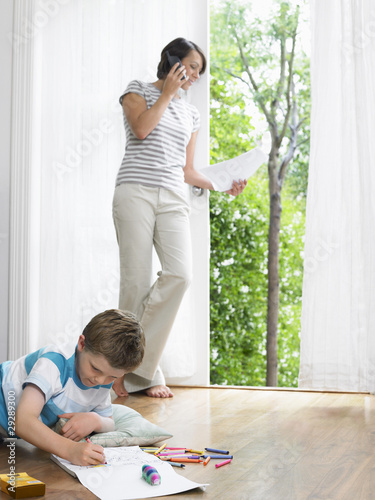 Mother using cell phone, young son drawing on floor