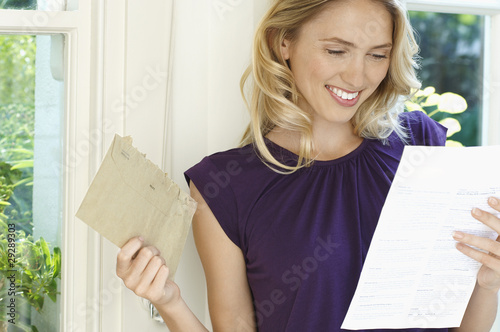 Woman looking at letter, looking happy