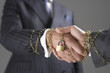Businessmen shaking hands wrapped in gold chain with padlock, close-up of hands