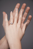 Young couple with hands raised together showing woman's engagement ring, close up on hands