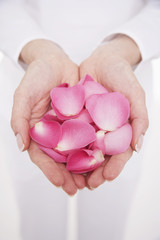 Woman cupping hands full of petals, mid section, close-up