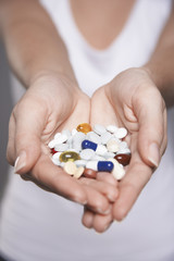 Woman holding pills in hands, close-up on hands