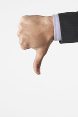Man making thumbs-down sign against white background, close-up of hand