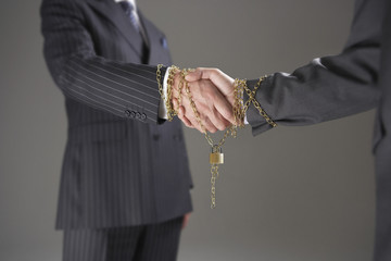 Businessmen shaking hands wrapped in gold chain with padlock, mid section