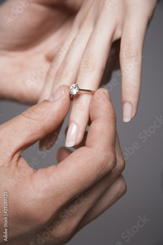 Man placing engagement ring on woman's finger, close-up of hands