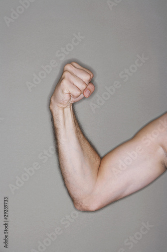 Man flexing biceps, close-up on arm