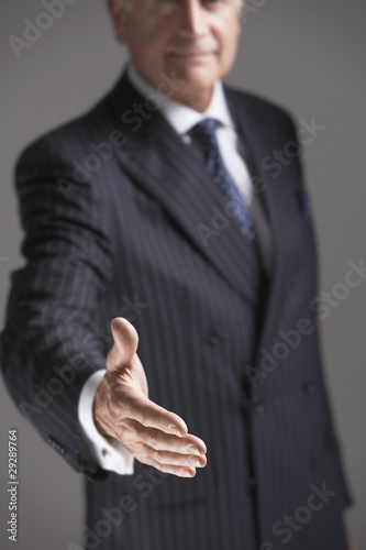 Businessman Offering Hand, half length