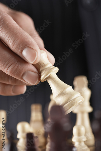 Man playing chess, close-up of hand holding piece