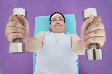 Overweight Man lying down Lifting dumbbells, overhead view