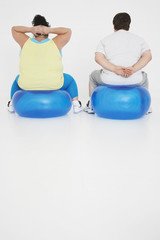 Overweight man and woman Exercising on exercise Balls, back view