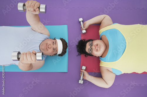 Overweight man and woman lying down lifting dumbbells, overhead view