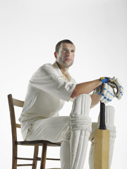 Cricket player sitting in chair, holding cricket bat, side view