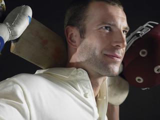Cricket player holding cricket bat behind shoulders, close-up