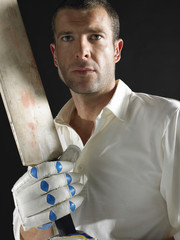 Cricket player holding cricket bat, portrait