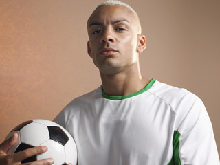 Football player holding ball, portrait