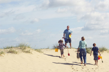 Vacationing Family walking up sand dune on Beach, back view