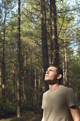 Worried man standing in woods looking up at canopy