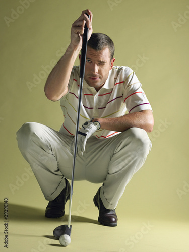 Golfer squatting, holding golf club and squinting