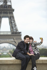 France, Paris, couple taking self portrait  in front of Eiffel Tower