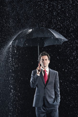 Businessman standing under sturdy Umbrella, hand in pocket