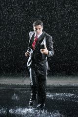 Businessman holding binder, running in Rain